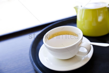 Tea pot : Cup of green tea on a tray with saucer and spoon