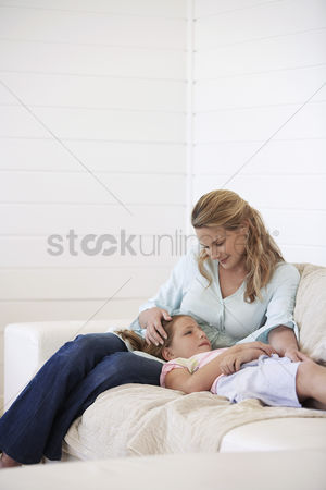 Sitting on lap : Daughter lying on mothers lap on couch