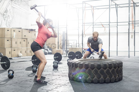 Strong : Dedicated man and woman hitting tire with sledgehammer in crossfit gym