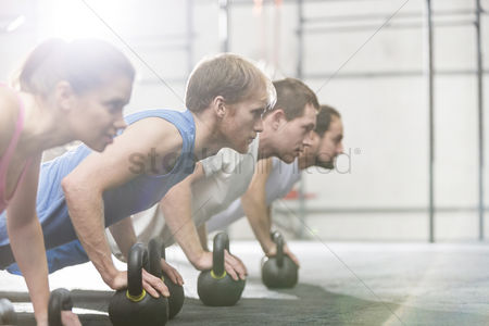 Fitness : Dedicated people doing pushups with kettlebells at crossfit gym