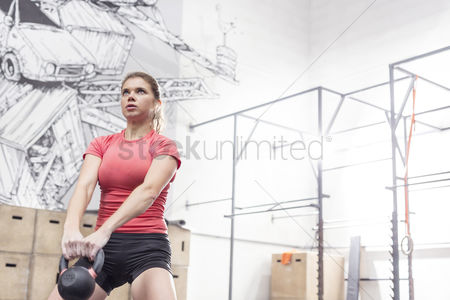 Fitness : Dedicated woman lifting kettlebell in crossfit gym