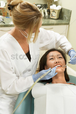 Pain : Dentist examining female patient in surgery