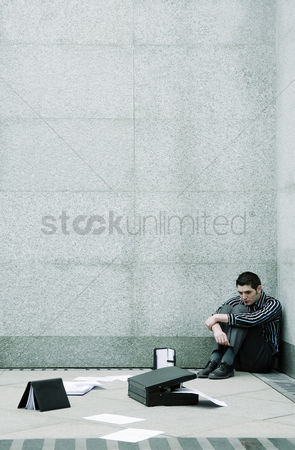 Profession : Depressed businessman sitting at the corner of a building