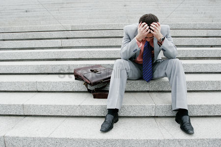 People : Depressed businessman sitting on the stairs