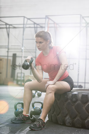Fitness : Determined woman lifting kettlebell in crossfit gym