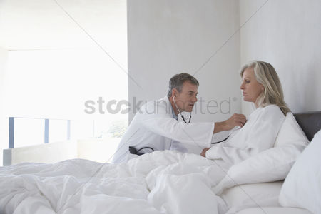 Seniors : Doctor doing house call on mature woman in bed using stethoscope side view