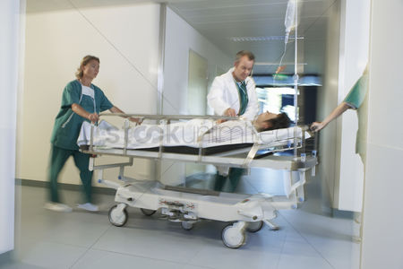 Expertise : Doctors moving patient on gurney through hospital corridor