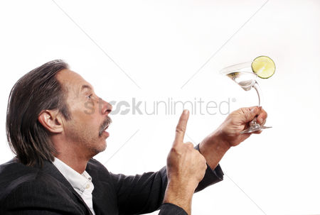 Having fun : Drunk businessman talking to a glass of alcoholic drink