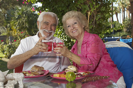 Toasting : Elderly couple with drinks in garden