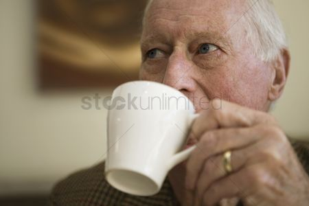 Bald : Elderly man holding cup