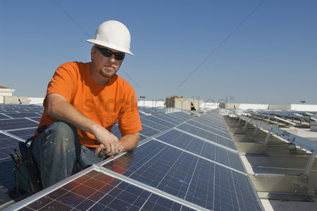 Posed : Electrical engineer among solar panels at solar power plant