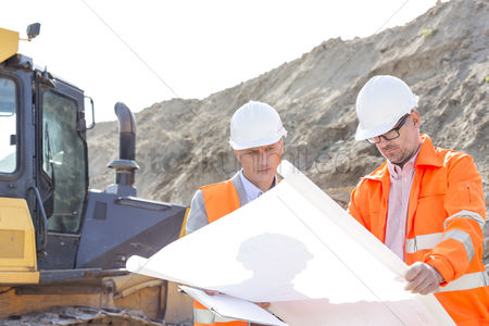 Supervisor : Engineers analyzing blueprint at construction site