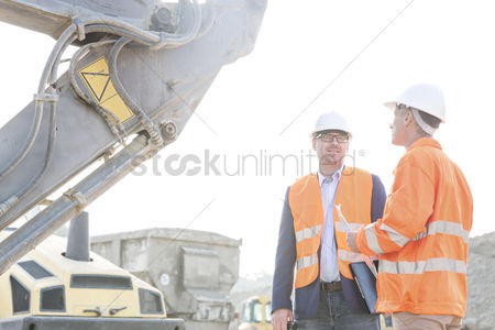Supervisor : Engineers discussing at construction site against clear sky