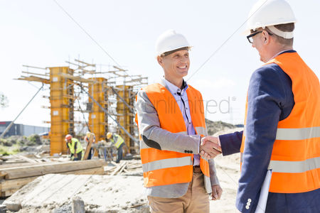 Three quarter length : Engineers shaking hands at construction site against clear sky