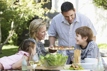 Pre teen : Family of four having lunch outdoors portrait