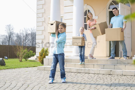 Women : Family with cardboard boxes moving out from house