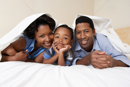 Curly hair : Family with son  3-6  lying underneath sheet portrait