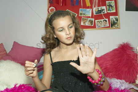 Maturity : Fashionable young girl applying nail polish in trendy bedroom
