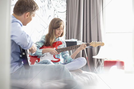 Pre teen : Father and daughter playing electric guitars at home