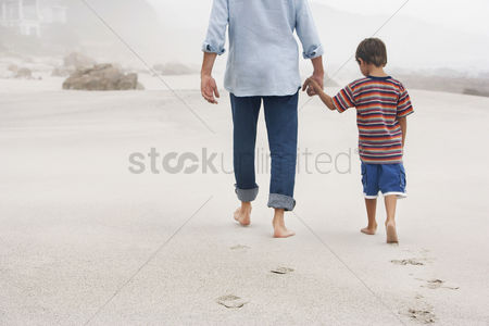 Mature : Father and son  5-6  holding hands walking on beach back view