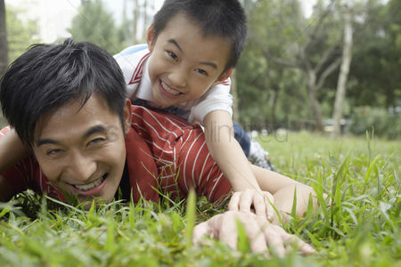 Grass : Father and son  7-9  in park lying in grass and laughing