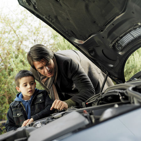 Fixing : Father and son checking the condition of their car