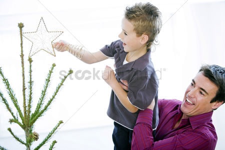 Maturity : Father and son decorating the christmas tree
