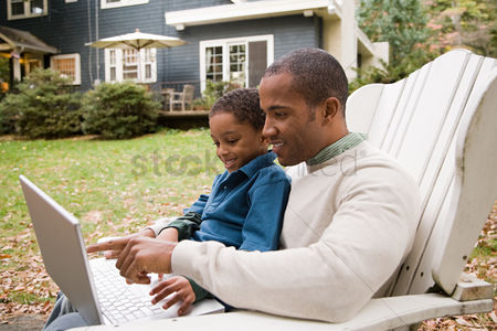 Sitting on lap : Father and son using laptop in garden