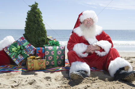 Jacket : Father christmas sits on the beach with a tree and presents