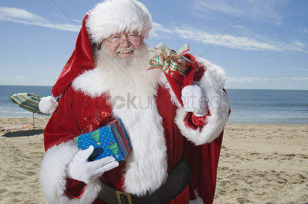 Jacket : Father christmas stands with his sack on a beach