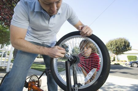Fixing : Father fixing son s bicycle tyre