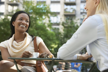 Office worker : Female colleagues sitting at street cafe
