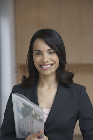 Cheerful : Female estate agent holding brochure smiling portrait