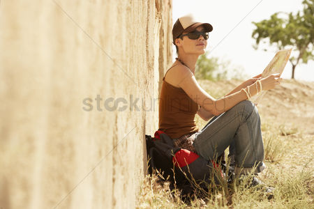 Resting : Female hiker holding map sitting on ground by rustic house