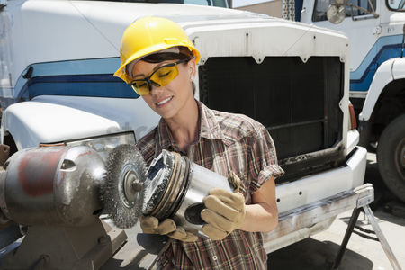 Land : Female industrial worker buffing a truck engine cylinder