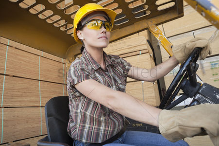 Forklift : Female industrial worker driving forklift truck with stacked wooden planks in background