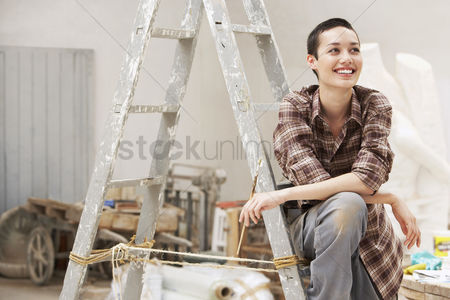Paint brush : Female interior decorator sitting on ladder in work site front view