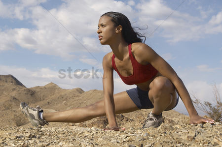 Young woman : Female jogger stretching in mountains