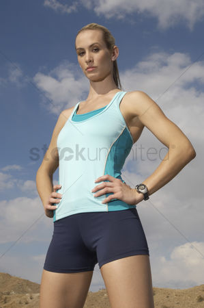 Proud : Female jogger with hands on hips outdoors portrait