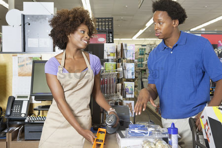 Supermarket : Female store clerk looking at customer while scanning product at super market