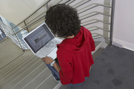 Pupil : Female student using laptop on stairs