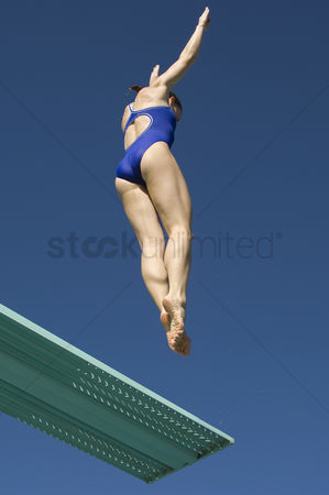 Diving : Female swimmer jumping on diving boards