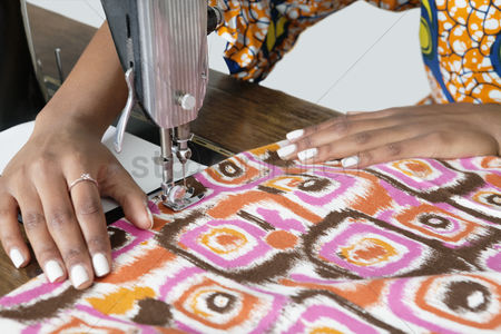 Fashion : Female tailor stitching patterned cloth on sewing machine