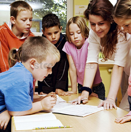 Children : Female teacher looking at a book with her students surrounding her