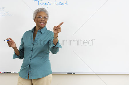 Teacher : Female teacher pointing by whiteboard in classroom