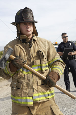 On the road : Firefighter with axe police officer in background