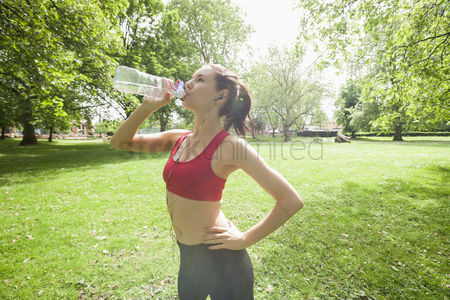 Three quarter length : Fit woman drinking water while listening to music in park