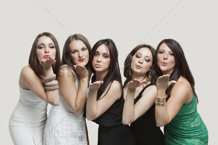Blowing : Five young women blowing kisses over gray background