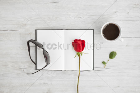 Floral : Flatlay of wooden background with rose and notebook