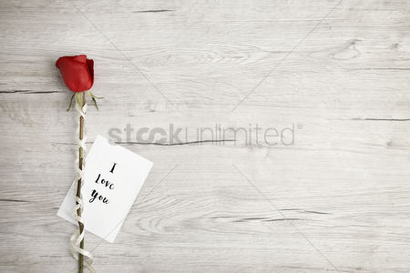 Flat : Flatlay of wooden background with rose and romantic message